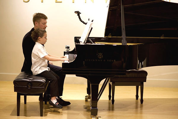The boy and a teacher play piano