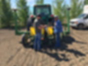 Bill the farmer and Jake (left) load the air seeder with squash seed