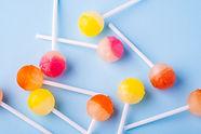 Scattered lollipop candies on blue backg