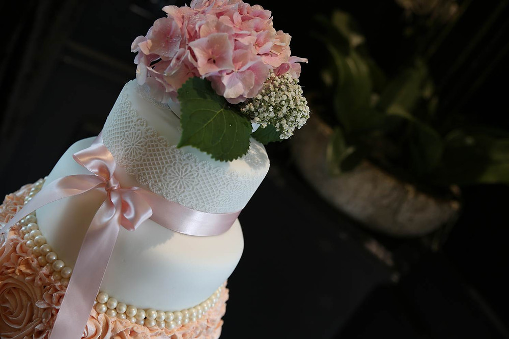 An elegant wedding cake with piped pink roses and a fresh flower topper