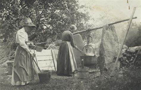black and white pic of woman cooking soap on a fire