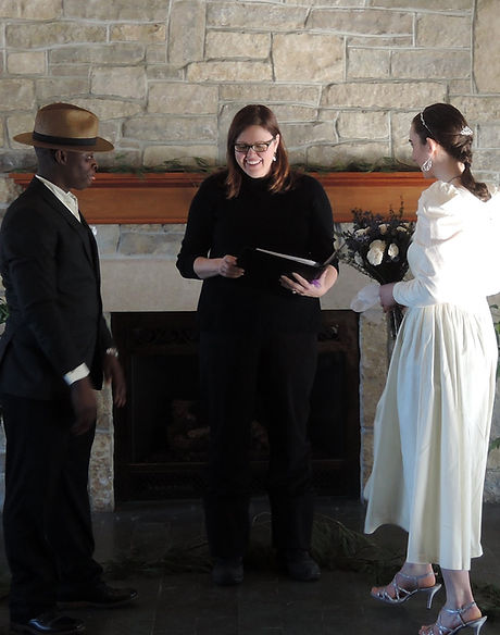 Officiant marrying a couple in front of a fireplace