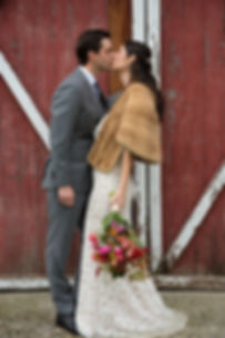 Couple kissing in front of a Vermont barn