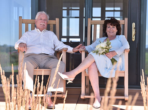 Older couple holding hands sitting in rocking chairs