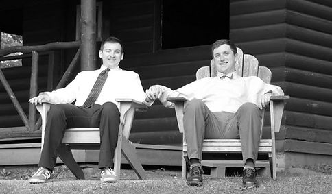 Gay Male Couple sitting in front of a log cabin