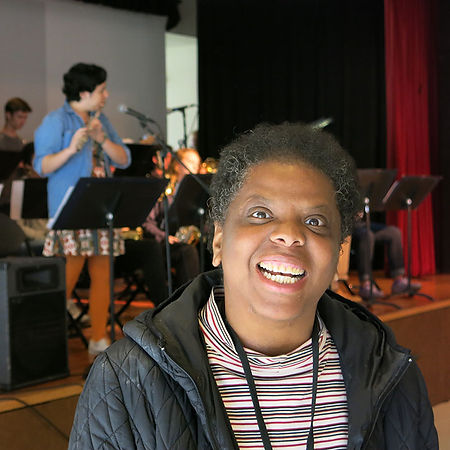African American older female participants with a hugesmile, a caucasian male on stage behind her playing the flute in frot of a mic and music stand