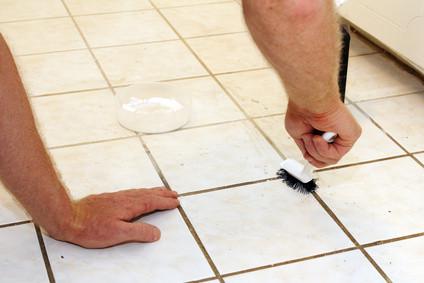 Ein Mann reinigt Fugen zwischen den Fliesen in einem Bad