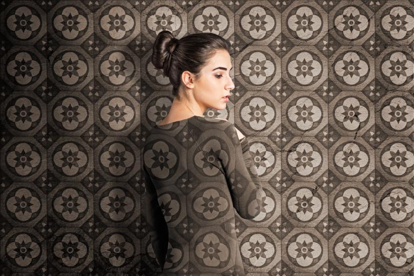 Eine Frau steht vor der Wand mit orientalischen Fliesen