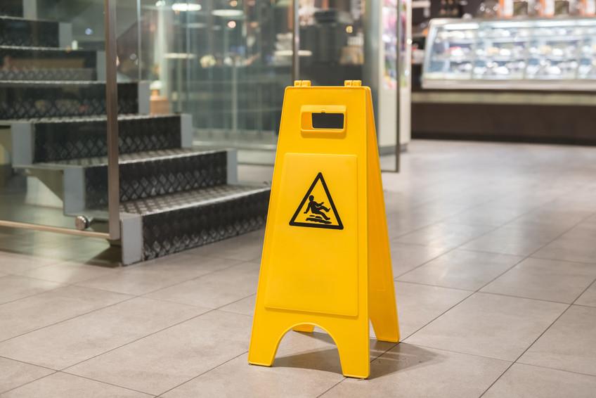"""Warnschild """"Vorsicht rutschig"""" steht auf nassen Fliesen im Einkaufszentrum"""