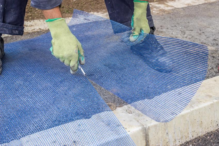 Eine Person schneidet eine Entkopplungsmatte durch und trägt dabei Handschue