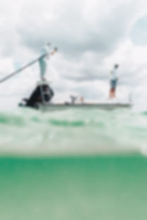 green-water-boat-pole-two-men