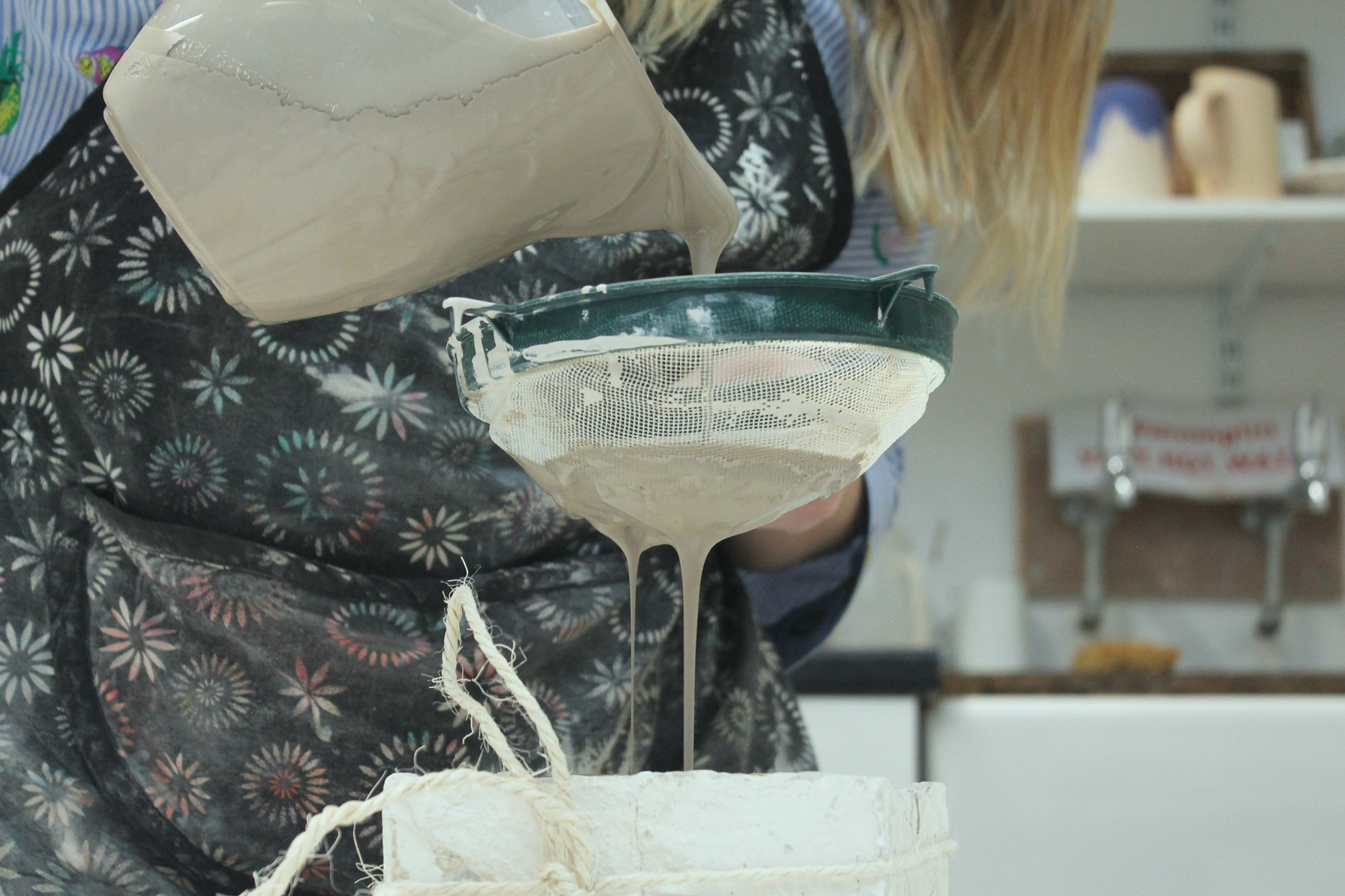 Pouring slip into the plaster mould to create casts.