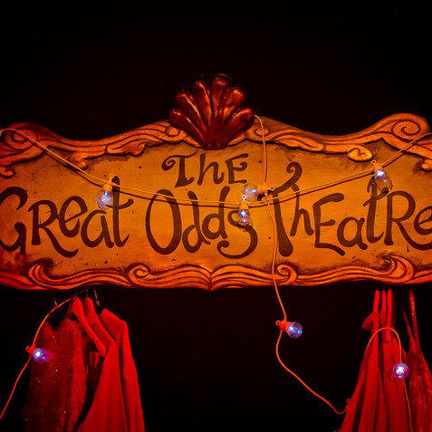 This final image is a production still from 'Great Odds'. It's a dark stage with golden lighting focussed on a vintage looking sign, decorated in a golden frame and topped with a shell, written on it in swirly handwriting is 'The Great Odds Theatre'