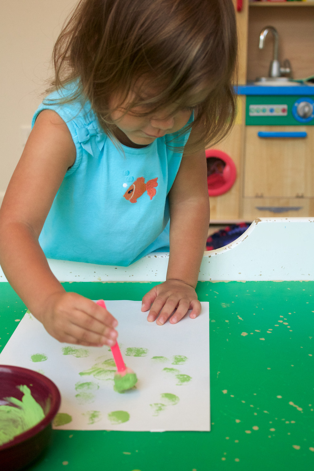 A Blue Sky Daycare home daycare child paints during a guided art project