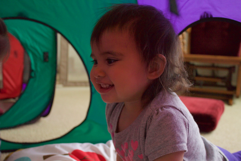 Blue Sky Daycare children enjoy crawling through tents and tunnels during movement activities