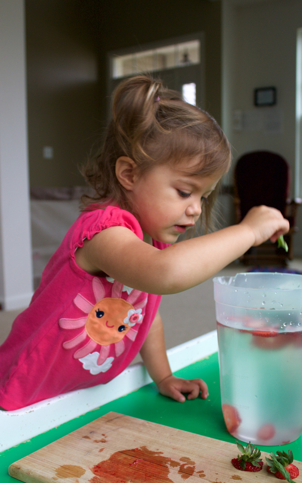 A Blue Sky Daycare child makes healthy flavored water with fruit and mint leaves