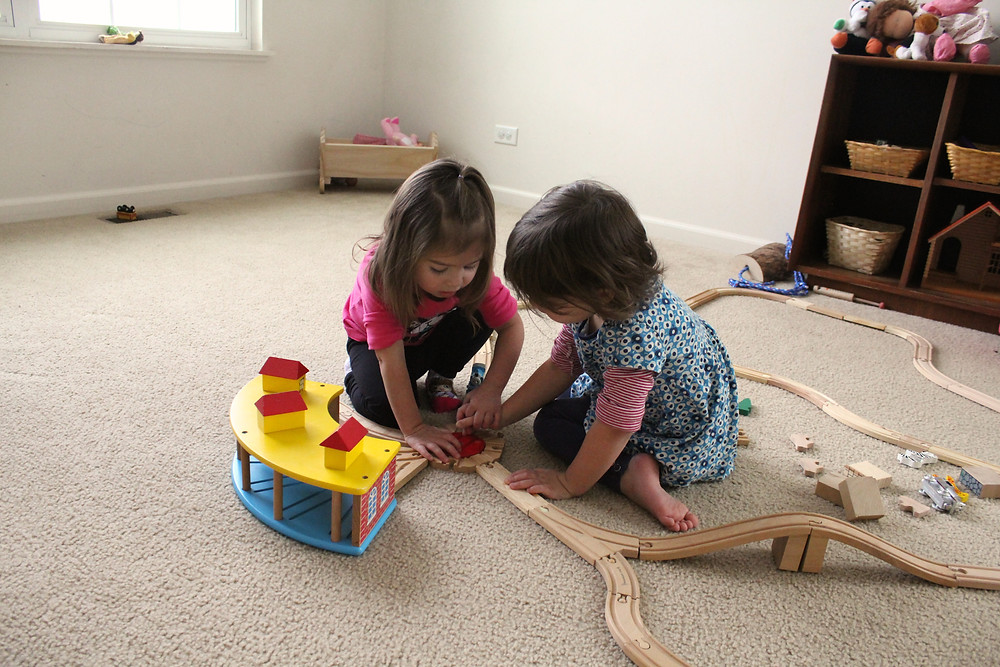 Blue Sky Daycare home daycare children playing with wooden train tracks