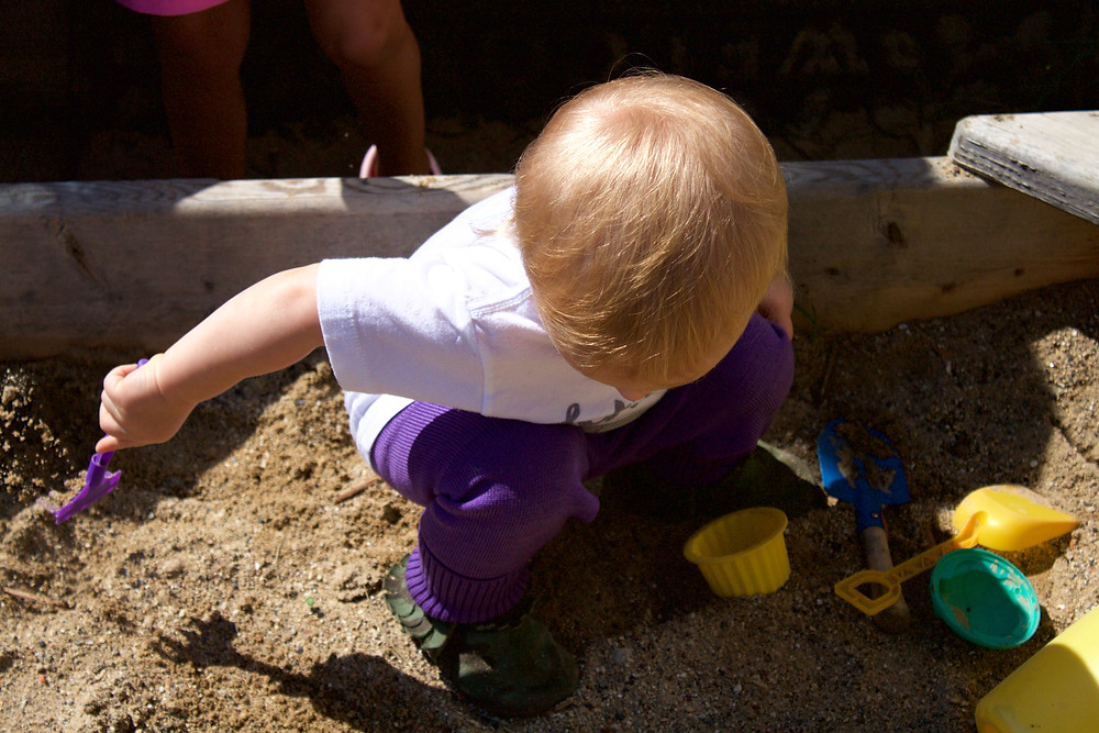 A new Blue Sky Daycare home daycare child explores in the sandbox