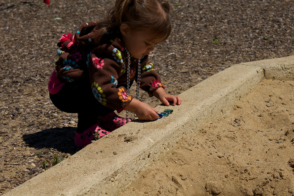 A Blue Sky Daycare home daycare child digs for buried treasure in the park sandbox
