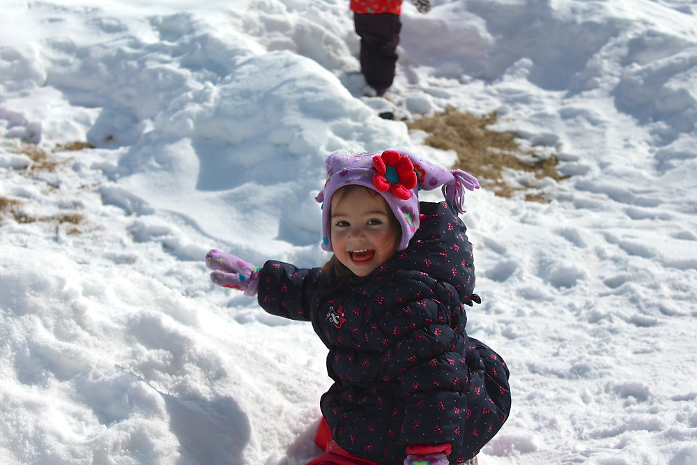 Blue Sky Daycare home daycare child crawling up a hill of snow
