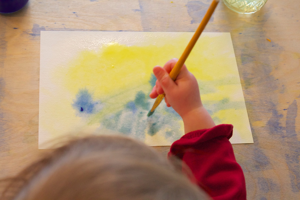 Blue Sky Daycare child watercolor painting during process art time