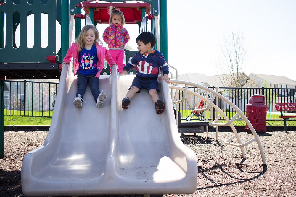 The Blue Sky Daycare children have a good time sliding at the park.
