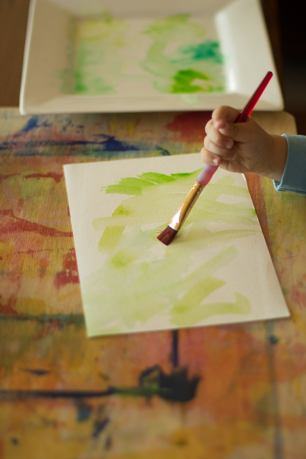 A Blue Sky Daycare child uses watercolors in a process art project.