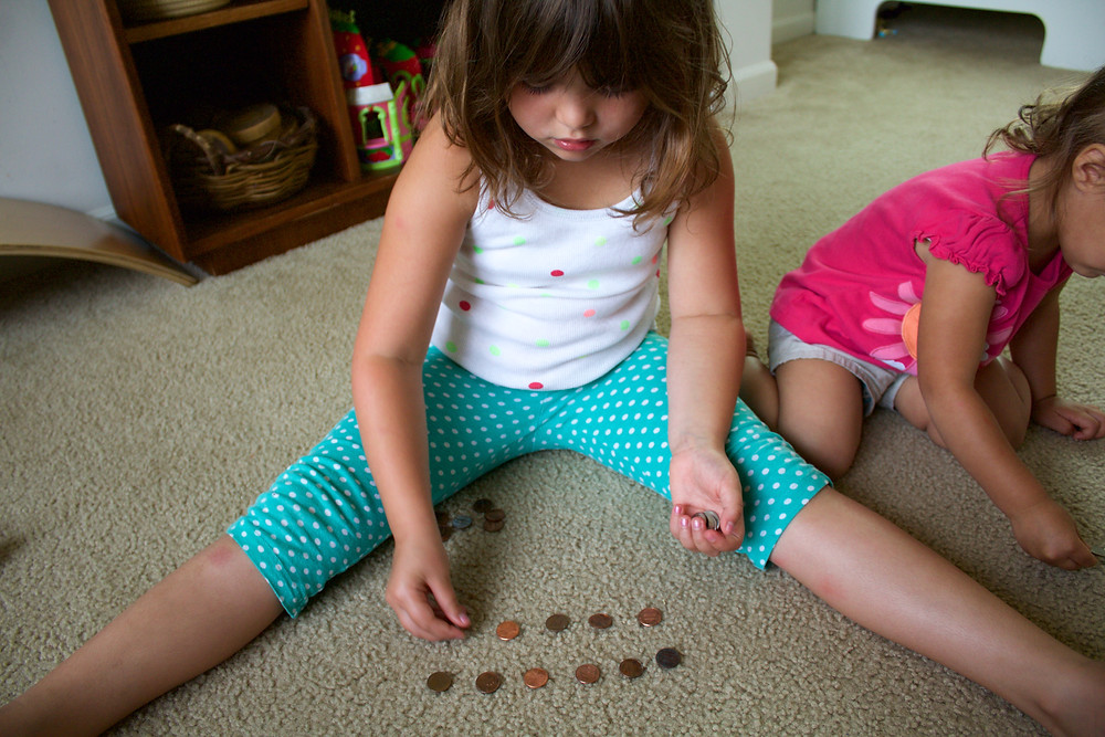A Blue Sky Daycare child practices counting out change