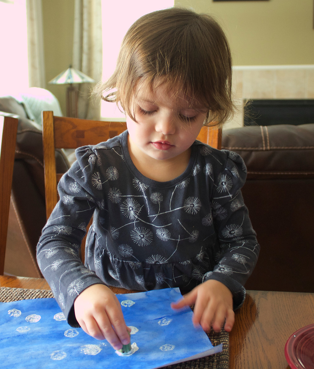 Stamping snowflake prints with okra at Blue Sky Daycare home daycare