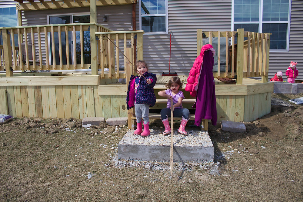 Blue Sky Daycare children playing pretend fishing during outdoor play time