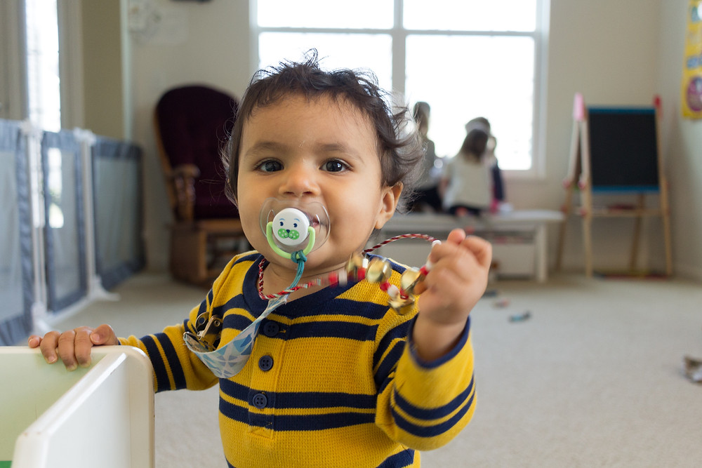 A Blue Sky Daycare child enjoys hearing the sound his jingling necklace makes