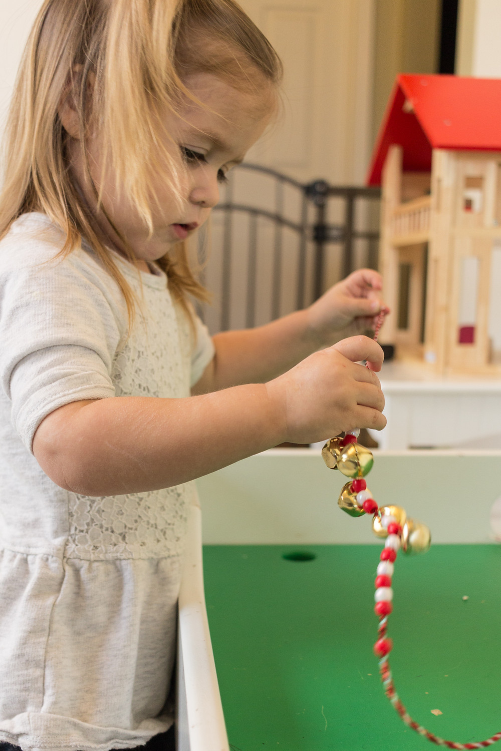 A Blue Sky Daycare child strings a jolly jingle necklace with beads and bells
