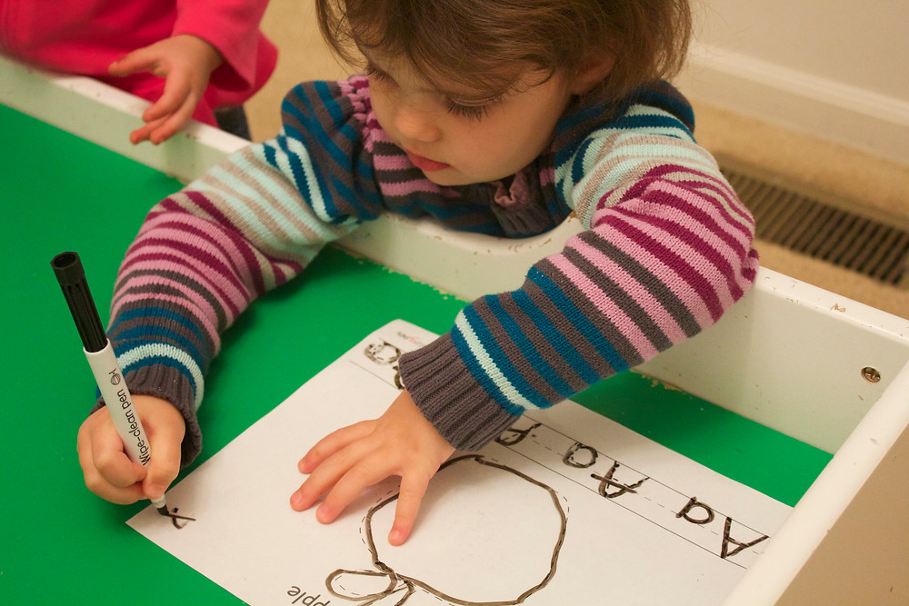 Blue Sky Daycare kids practice early literacy and fine motor skills
