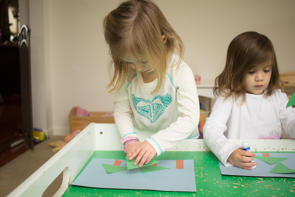 A Blue Sky Daycare child uses simple shapes to create artwork.