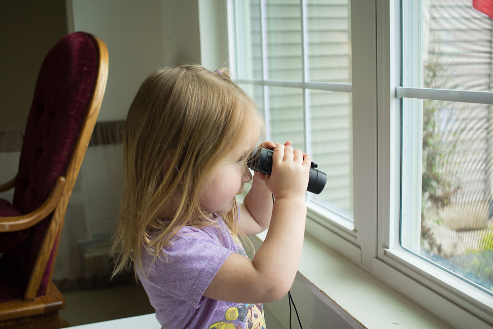 A Blue Sky Daycare kid has a fun time looking for birds with binoculars.