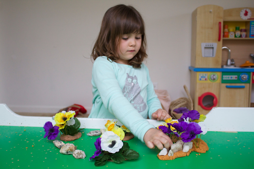Process art with play dough and faux flowers at Blue Sky Daycare home daycare