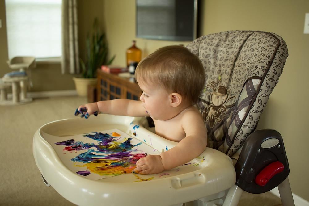 The littlest Blue Sky Daycare child explores fingerpainting