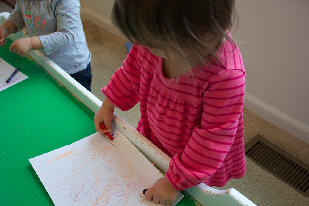 Blue Sky Daycare home daycare child coloring with crayons during process art time
