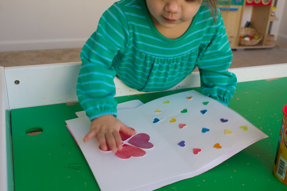 Blue Sky Daycare child doing a guided art Valentine's Day project