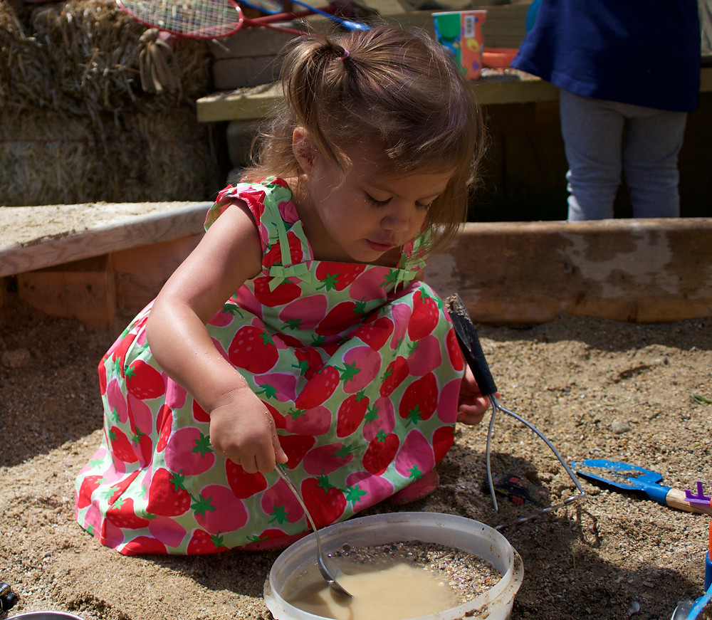 Blue Sky Daycare home daycare child creates pretend soup in mud kitchen