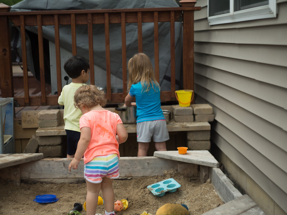 Children enjoy playing in the mud kitchen and sandbox at Blue Sky Daycare