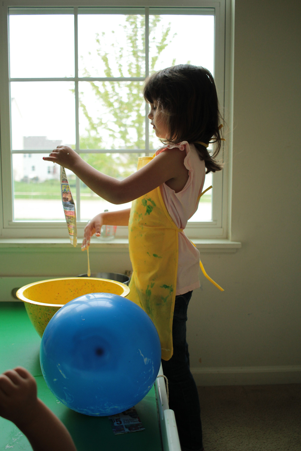Blue Sky Daycare children cover a balloon with strips of paper mache for a piñata