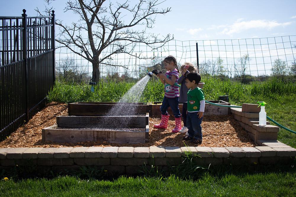 Blue Sky Daycare children taking care of tiny flower garden plants
