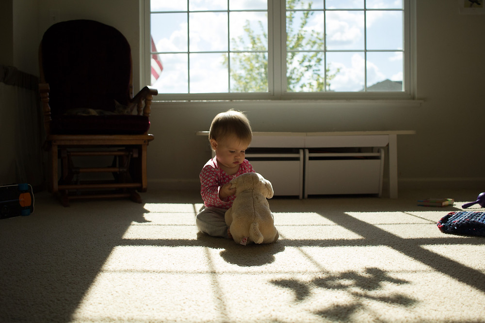 A moment of innocence as a Blue Sky Daycare child examines a toy