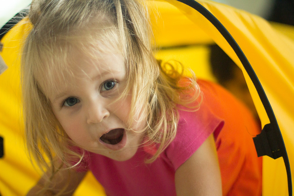 A Blue Sky Daycare child has fun playing in tunnels.