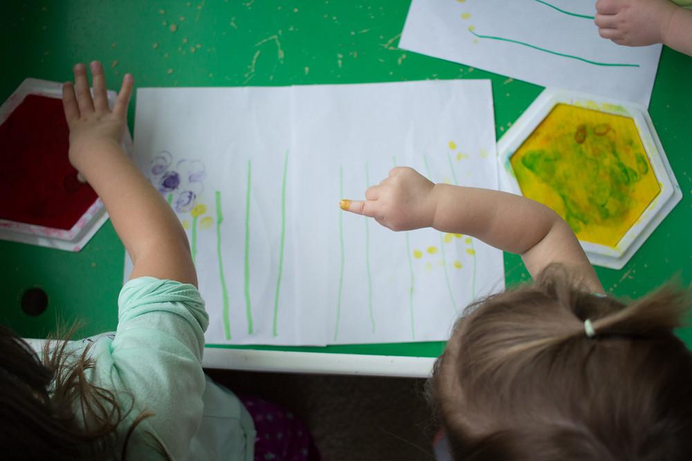 Blue Sky Daycare children make fingerprint art.