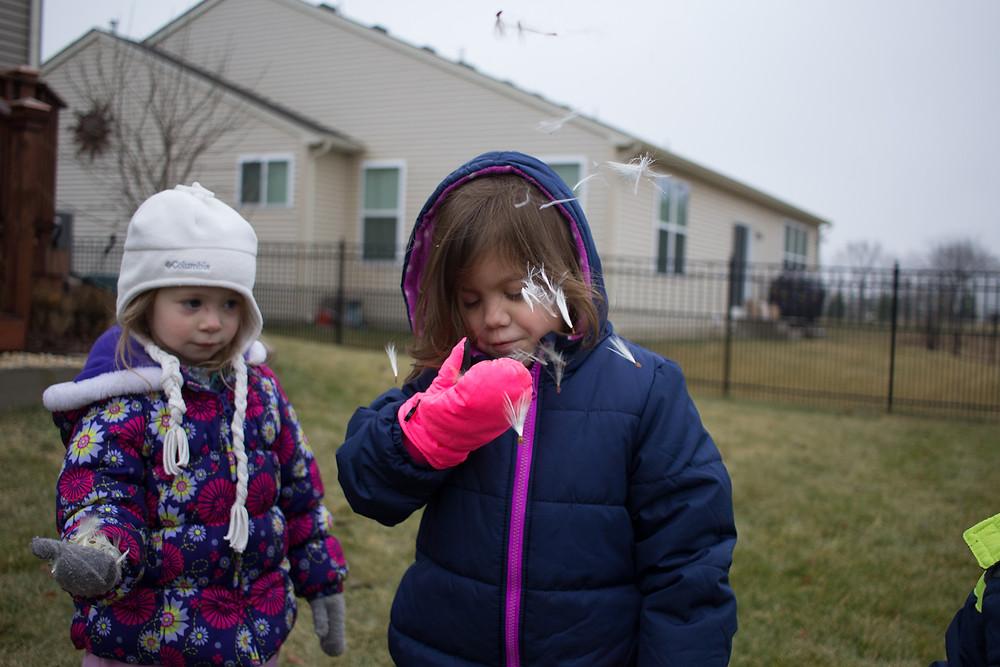 Blue Sky Dacyare children enjoy blowing milkweed puffs.