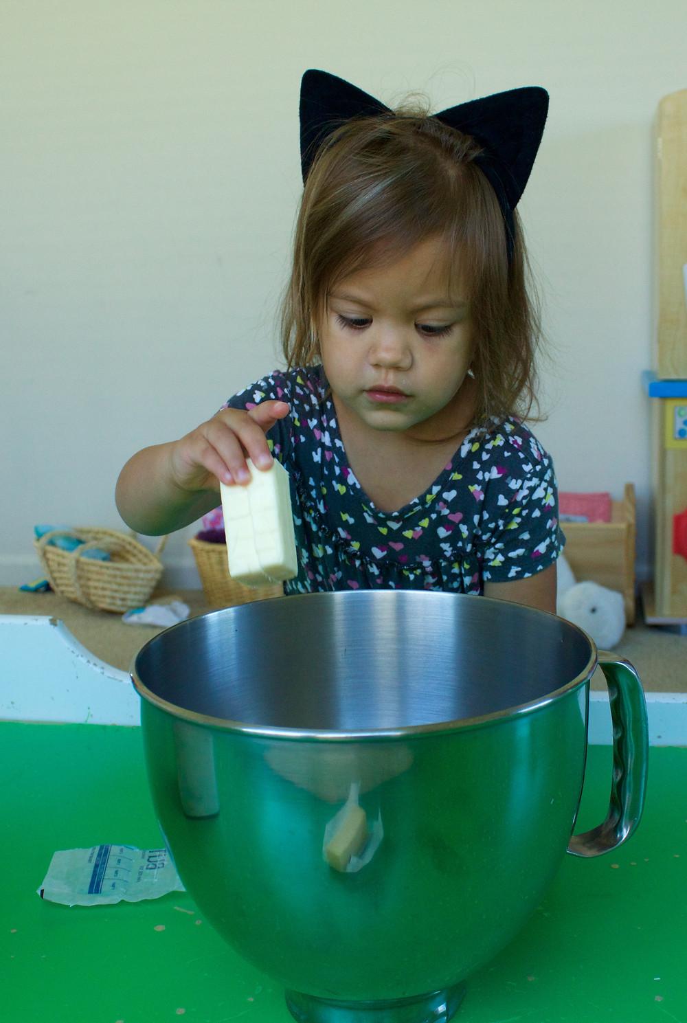 A Blue Sky Daycare home daycare child helps prepare birthday cake