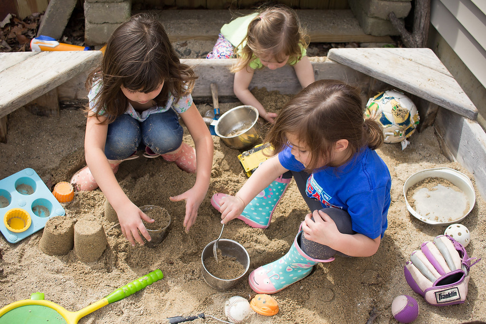 The Blue Sky Daycare children have fun in the sandbox.