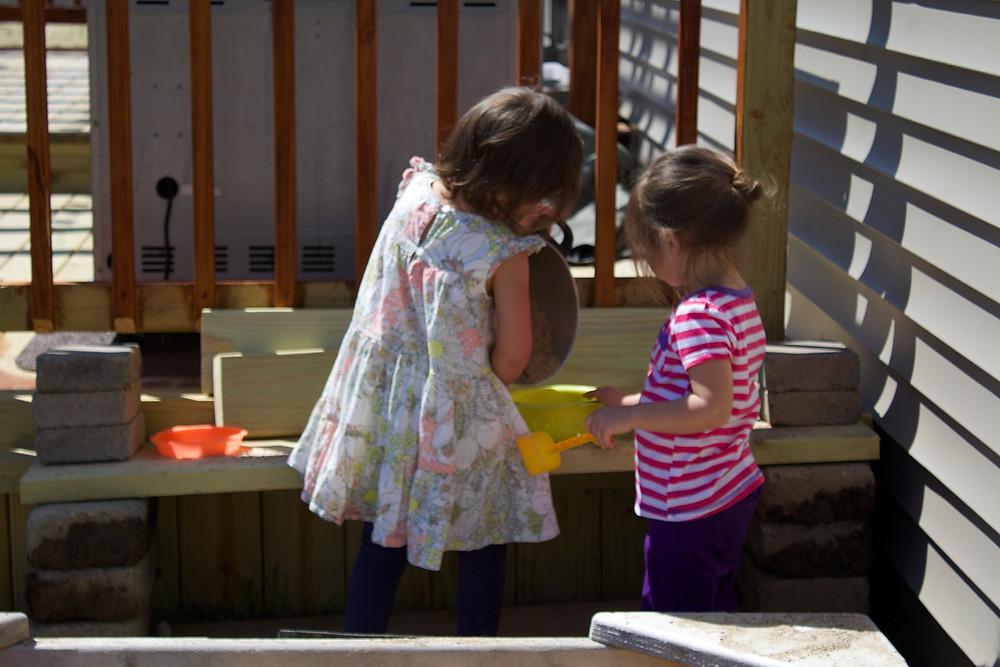 Setting up an outdoor mud kitchen at Blue Sky Daycaree home daycare